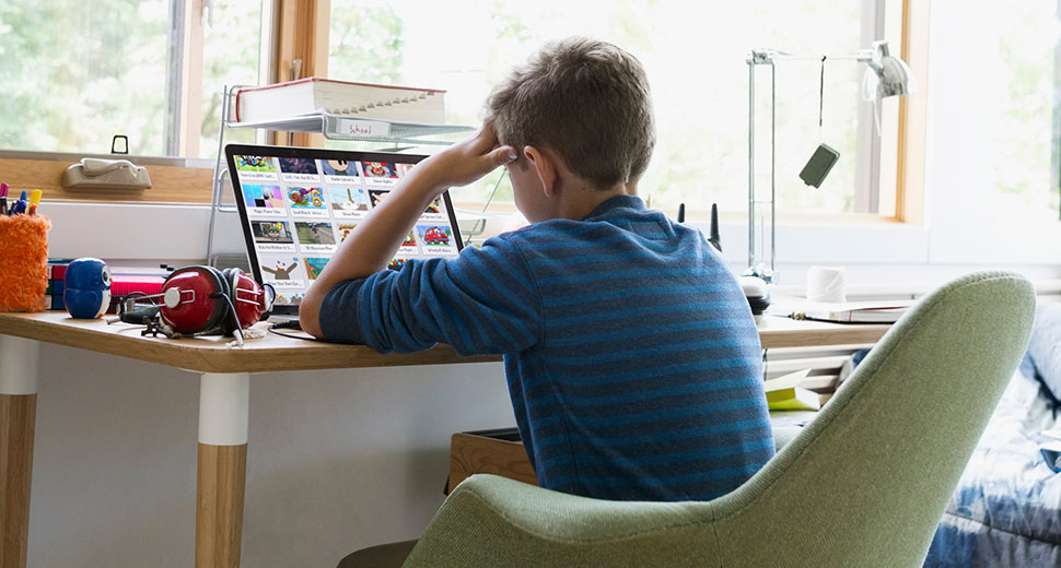 Boy sits at his desk whilst working on a laptop