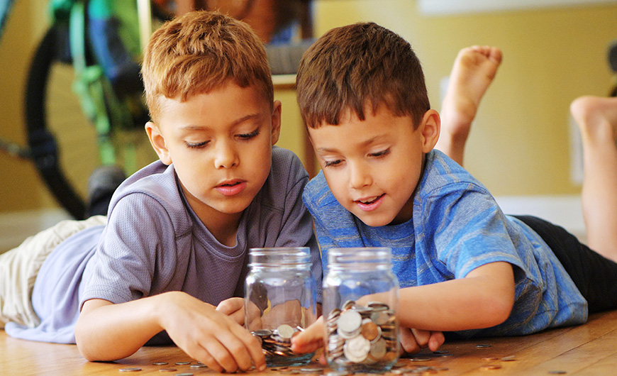 Two young boys counting their money and putting it into money jars