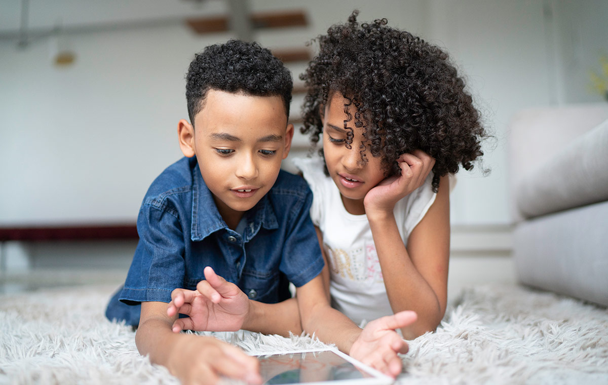 Two children play together on an iPad