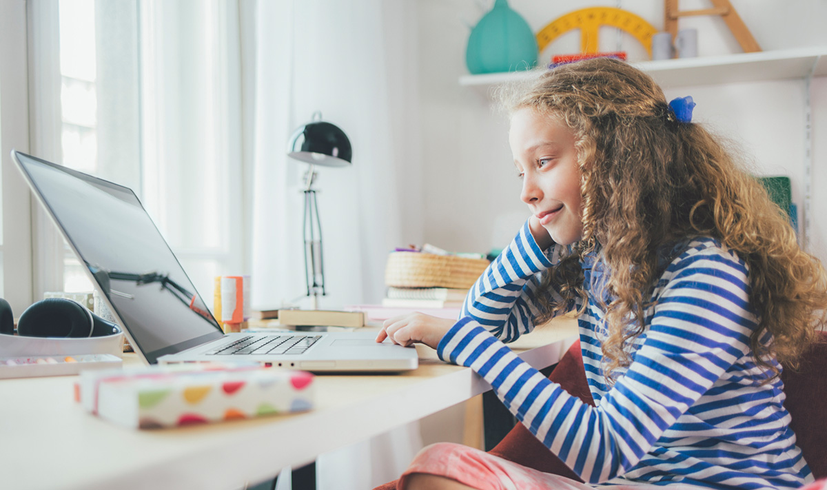 A young girl sits at her desk and works on her laptop