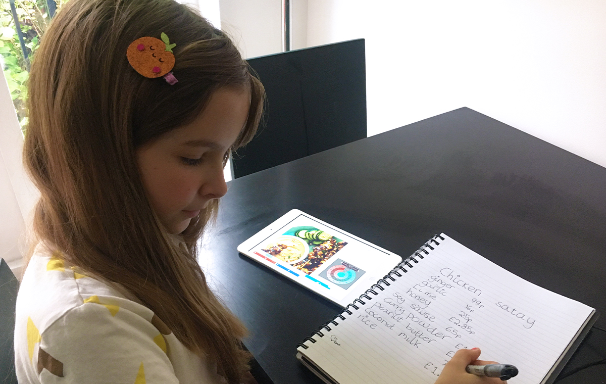 A young girl counts writes up a shopping list for a new recipe
